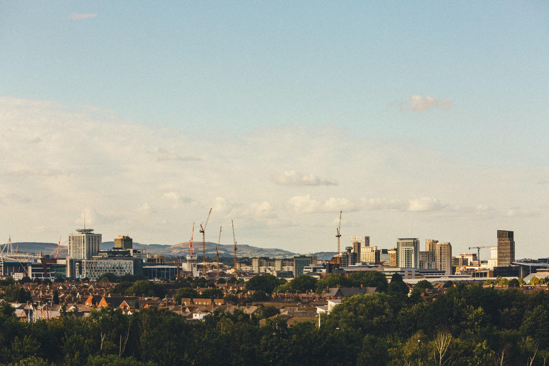 Image is a landscape photo of Cardiff's skyline in day time with a sunny blue sky and a few clouds.