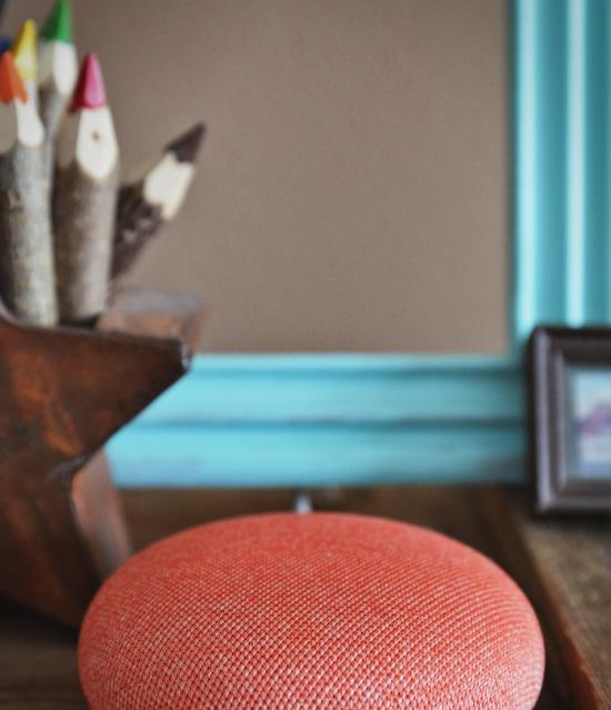 Photo of a Google Home resting on a desk with a pot of coloured pencils in the background.