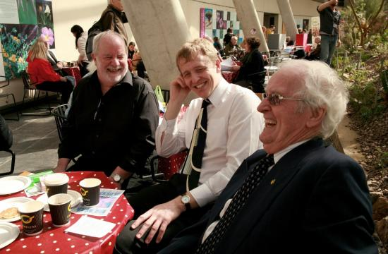 A group of older men with white hair wearing shirts and ties talking and laughing around a table.