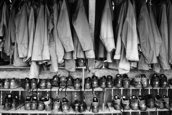 ID: black and white image shows a row of coats hung in a shed over several pairs of boots in a row at Down to Earth on the Gower.