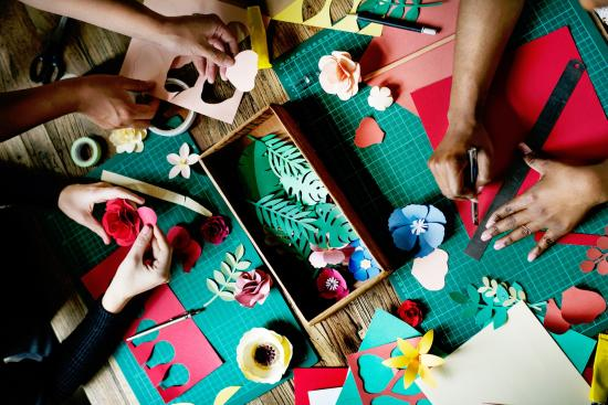 ID: an aerial photo of various crafting materials including cutting mats, coloured card cut into plant and flower shapes and pens. There are three pairs of hands working on these crafts in the  image.