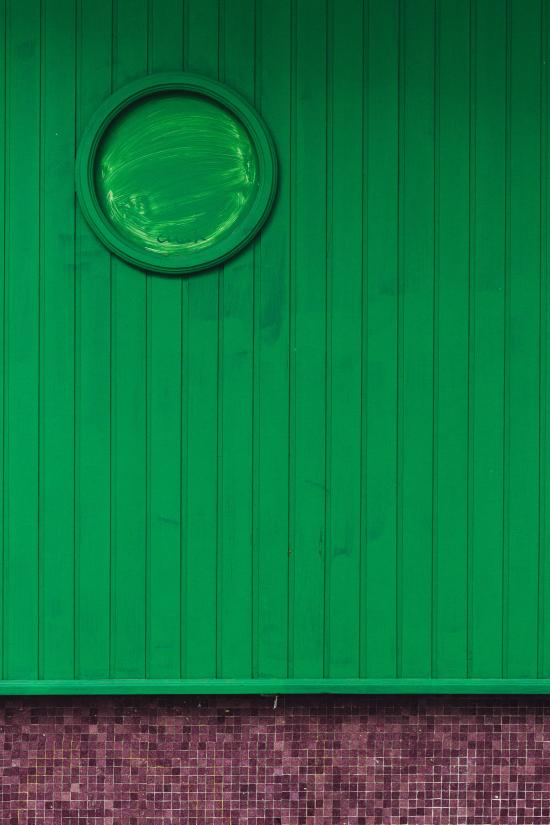 Image shows a green wooden-slatted wall with a painted over porthole.