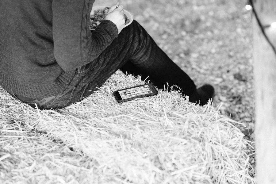 Man sitting on a hay bale with a plate and a phone resting beside him.