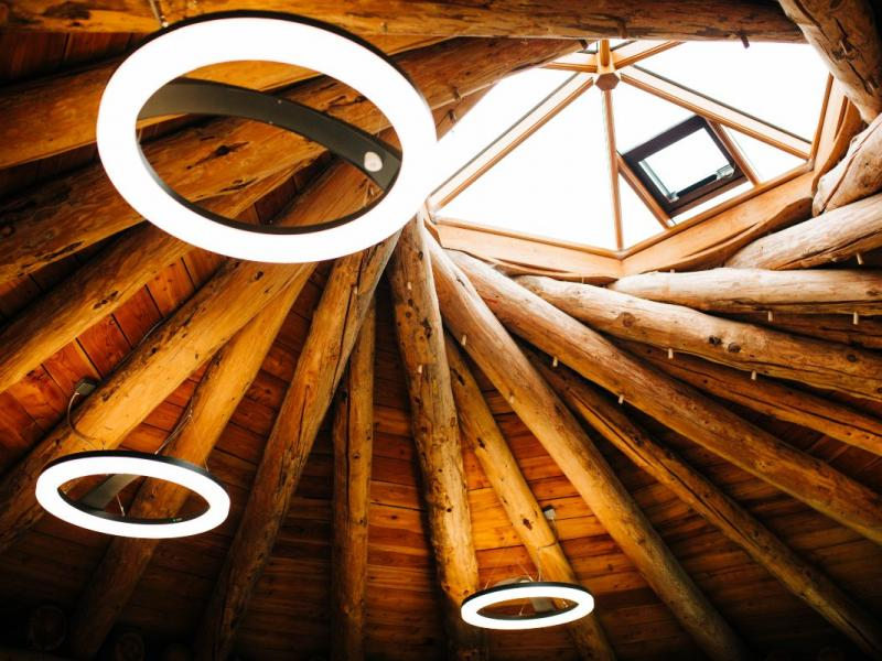 Image of the inside of a ceiling of a wooden-beamed building with circles of light and a window