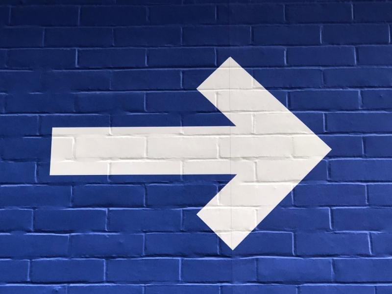 Image of a blue brick wall with a large white arrow pointing right.