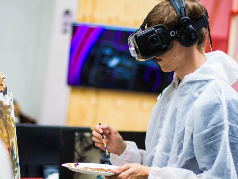 Image shows a person wearing a virtual reality headset painting with a palette and canvas