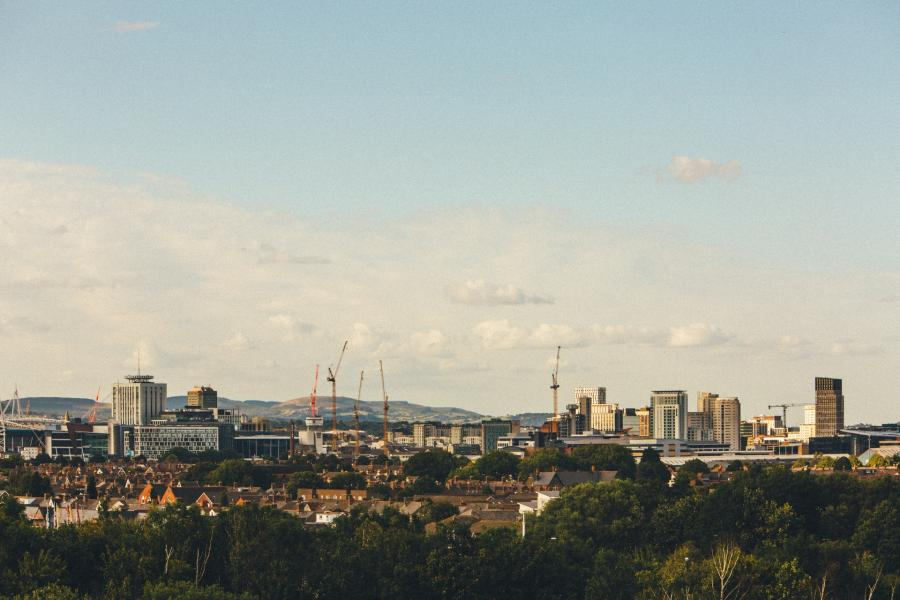 Image shows a landscape view of the Cardiff skyline with tall buildings and cranes against a blue sky with clouds.